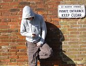 stock photo of loafers  - A hooded youth on his phone by a keep clear sign - JPG