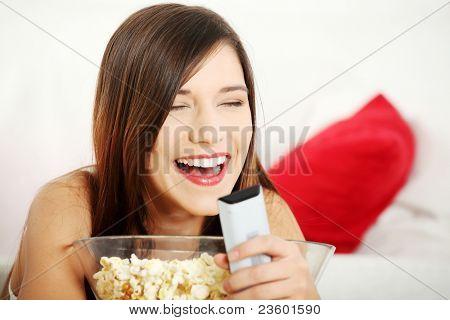 Girl watching TV having fun eating popcorn.