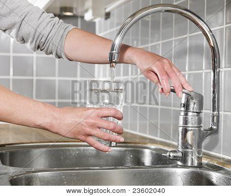 füllen ein Glas Wasser