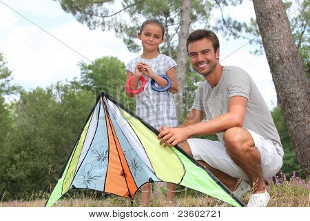 a father and his daughter with a kite