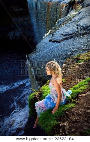 beautiful girl on brink ofriver waterfalls