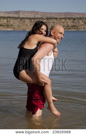 Woman On Mans Back In Water