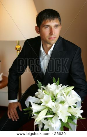 Smiling Groom Holding A Bouquet