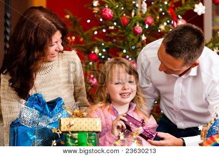 Christmas - happy family (parents with daughter) with gifts on Xmas Eve