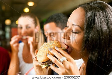 Friends - one couple is African American - eating hamburger and drinking soda in a fast food diner; focus on the woman in front