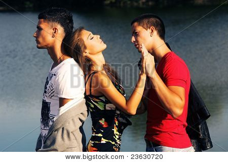 love triangle, two young men and young woman on the beach at sunset