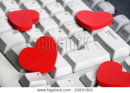 Love or online dating concept red heart shape symbol on white computer keyboard