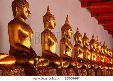 A Row Of Golden Buddha Statue At Wat Pho, Thailand Temple