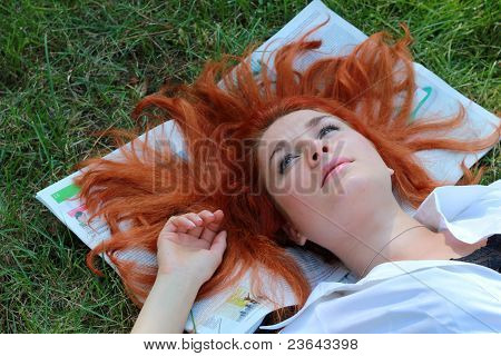 Beautiful young girl lying on the newspaper