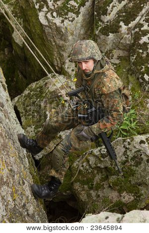 Armed Soldier Hanging On A Cliff