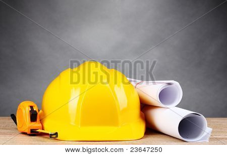 Construction tools on wooden table on gray background