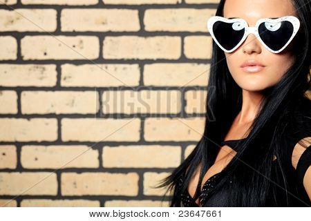 Fashion photo, a model is posing over brick wall.