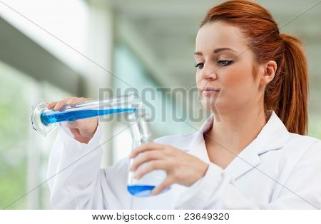 Young Scientist Pouring Blue Liquid In An Erlenmeyer Flask