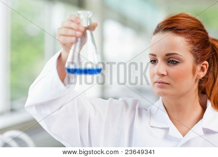 Science Student Looking At A Blue Liquid