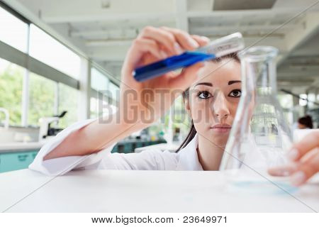 Focused Science Student Pouring Liquid