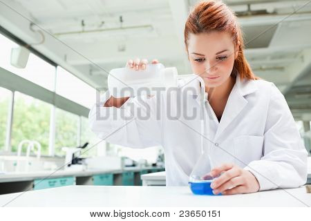 Red-haired Focused Scientist Pouring Liquid In A Flask