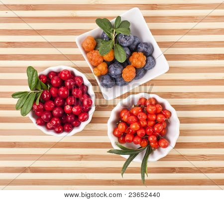 Fresh berries in a  wooden  surface