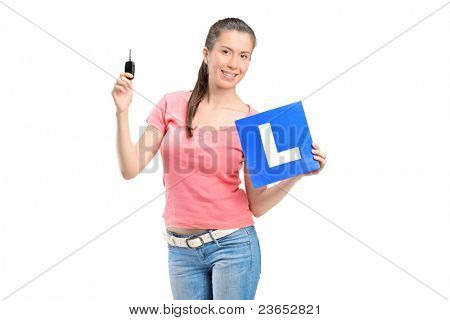Happy teenager holding a L plate and a car key isolated on white background