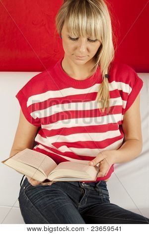 Young Woman Sitting On A Sofa Reading Book