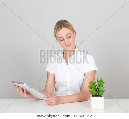 Woman sitting by green plant with electronic tablet