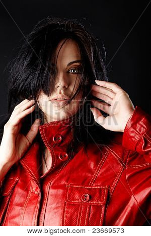beautiful woman in red leather jacket and blowing hair on dark studio background.