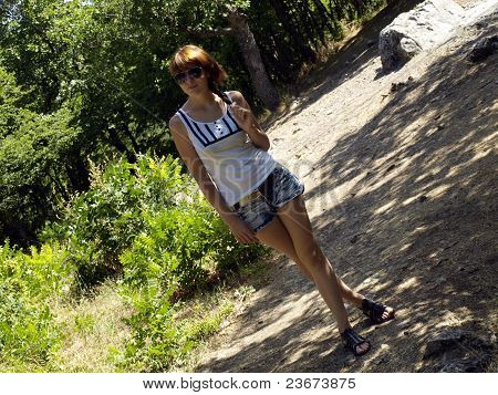 The girl walks in wood in shorts and a T-shirt