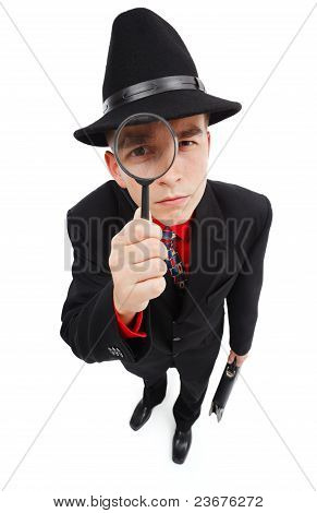 Serious Detective Looking Through Magnifying Glass