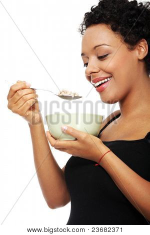 Young pregnant woman eating muesli, isolated on white background
