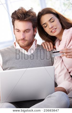 Young couple shopping on internet, having laptop, using credit card.?