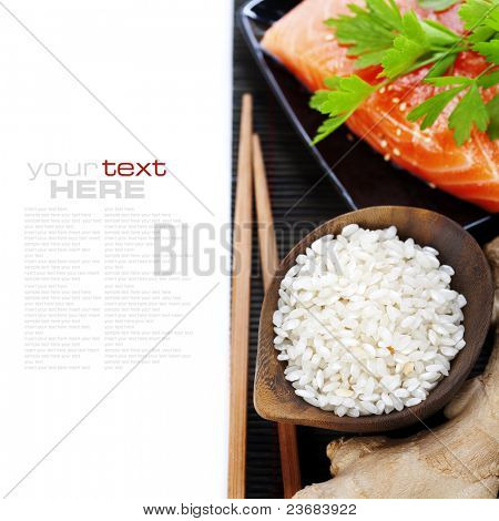 traditional asian ingredients (Fresh salmon steak filet, uncooked rice, ginger and chopsticks) over white with sample text