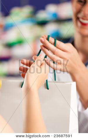 Female pharmacist with a female customer in her pharmacy