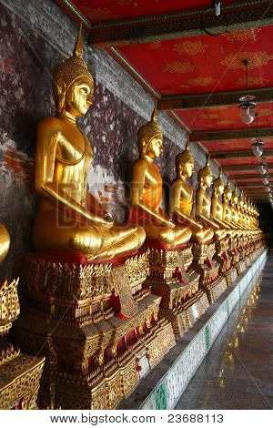 A Row Of Golden Buddha Statue At Wat Suthat In Thailand