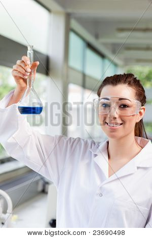 Portrait of a female science student holding a blue liquid in a laboratory