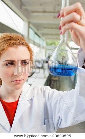 Portrait of a cute science student holding a blue liquid in a laboratory