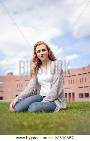 Portrait of a young woman sitting on a lawn in front of an IT
