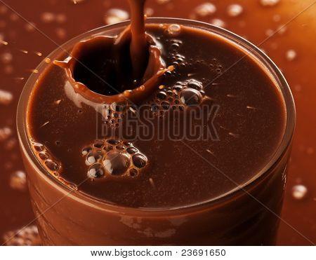 extreme closeup of Chocolate splashing on glass
