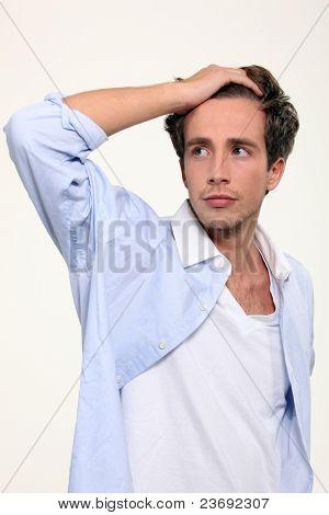 Junger Mann mit seiner Hand durch sein Haar