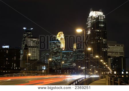 Minneapolis City Skyline At Night With Bridge And Moving Cars