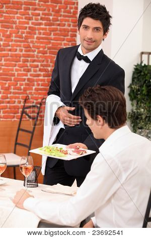Waiter deliver in meal in restaurant