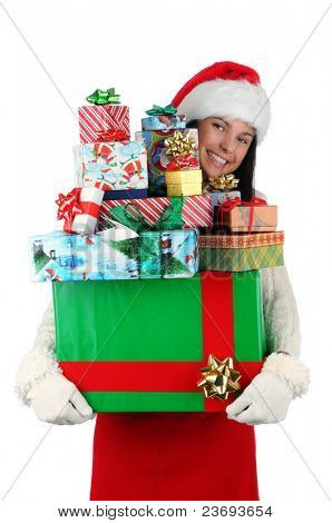 Woman carrying a large stack of christmas presents isolated on white. Woman is peeking around the side of the gifts. Vertical format.