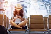 Asian Woman Teenager Using Smartphone At Airport Terminal Sitting With Luggage Suitcase And Backpack poster