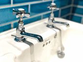Metal faucet tap sink basin in a trendy contemporary bathroom with blue tiles poster