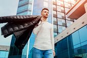 Arabian Man Holding His Coat And Walking In City Center. Young Man Throws Coat On Shoulder. Fashion poster