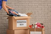 Volunteer Collecting Clothes Into Donation Boxes Indoors poster