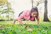 Asian Young Woman Warm Up Her Body By Push Up To Build Up Her Strength Before Morning Jogging Exerci poster