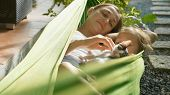 Happy Mother And Daughter Relaxing Together In A Hammock With Cat At Garden In Sunny Summer Day. Fam poster