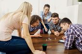 A Group Of Friends Play Board Games On The Floor Having Fun At A Party Indoors. poster