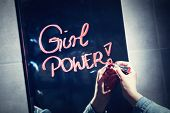 Woman writing girl power on a mirror with red lipstick. Woman empowerment. Feminism. poster
