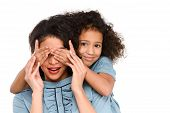 Daughter Covering Eyes Of Surprised Mother With Hands Isolated On White poster