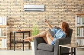 Young woman switching on air conditioner while sitting in armchair at home poster